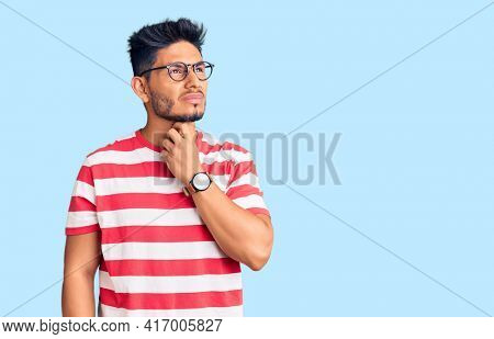 Handsome latin american young man wearing casual clothes and glasses touching painful neck, sore throat for flu, clod and infection