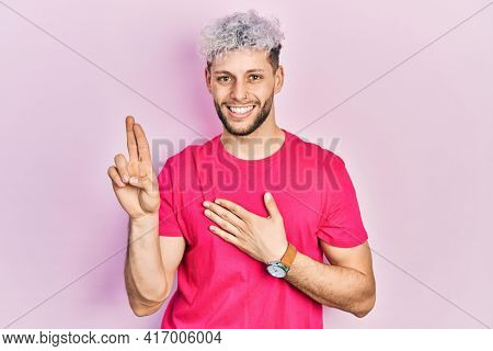 Young hispanic man with modern dyed hair wearing casual pink t shirt smiling swearing with hand on chest and fingers up, making a loyalty promise oath