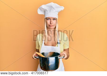 Young blonde girl cooking spaghetti skeptic and nervous, frowning upset because of problem. negative person.