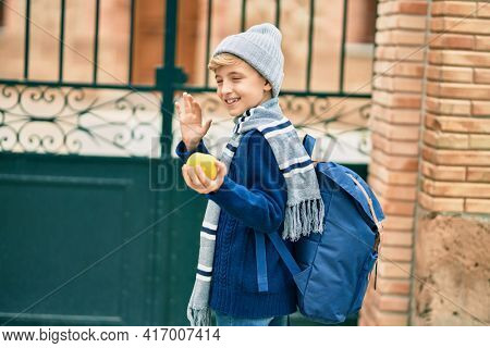 Adorable blond student kid saying goodbye with hand getting in the school.