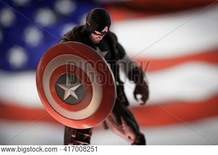 APRIL 14 2021: Marvel comics Avenger Captain America with shield and American Flag, looking down - Hasbro action figure