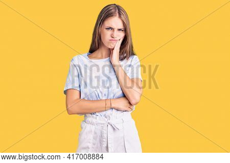 Young beautiful blonde woman wearing tye die tshirt thinking looking tired and bored with depression problems with crossed arms.