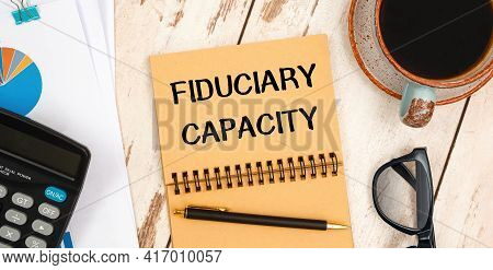 Notebook With Text Fiduciary Capacity On The Office Table, Documents, Calculator, Glasses And Pen