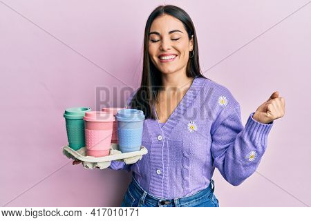 Young brunette woman holding tray with take away coffee screaming proud, celebrating victory and success very excited with raised arm