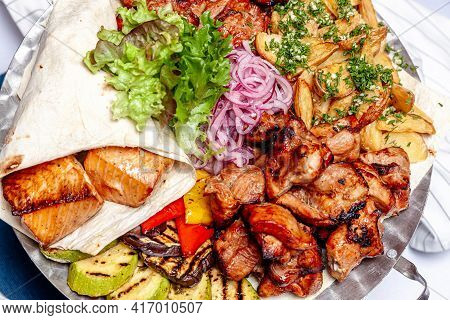 Mixed Grill Meat Fried Vegetables And Grilled Salmon Fish Fillets Decoration In Warm Dish. Assorted