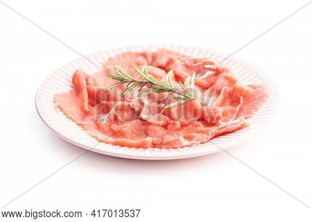 Sliced carpaccio. Raw beef meat on plate isolated on white background.
