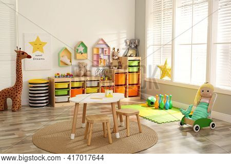 Stylish Playroom Interior With Soft Toys And Modern Furniture