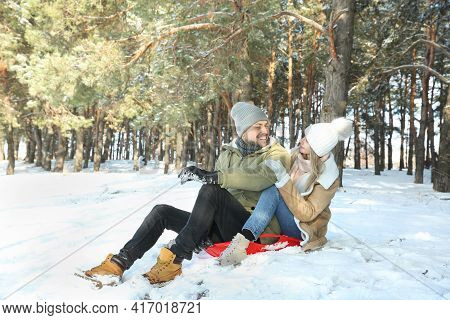 Happy Couple Sleighing Outdoors On Winter Day