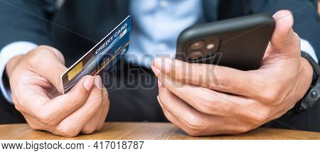 Businessman In Suit Holding Credit Card And Using Touchscreen Smartphone For Online Shopping While M