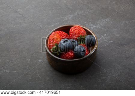 Strawberries And Blueberries In A Small Cup On A Black Background