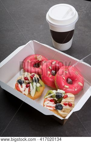 Paper Coffee Cup And Different Donuts Box On A Dark Background