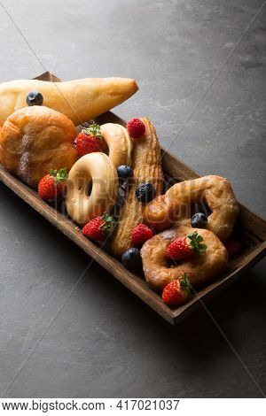 Different Types Of Donuts Served With Berries On Wooden Tray