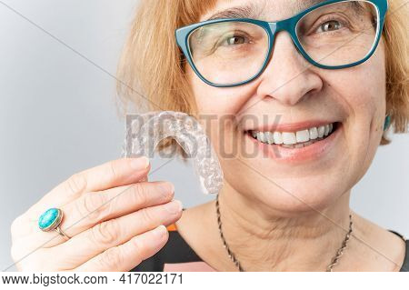 A Happy Elderly Woman Puts On Transparent Removable Braces. Cosmetic Dentistry For All Ages
