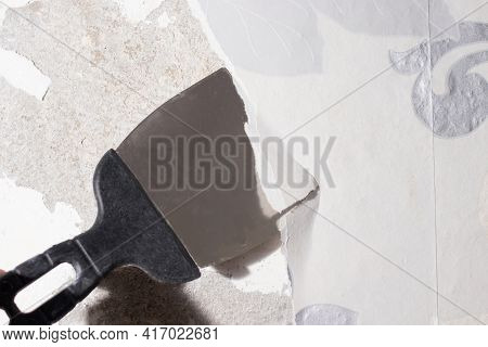 The Repairman Removes Old Dangling Wallpaper From The Wall With A Spatula. Removing Wallpaper Residu
