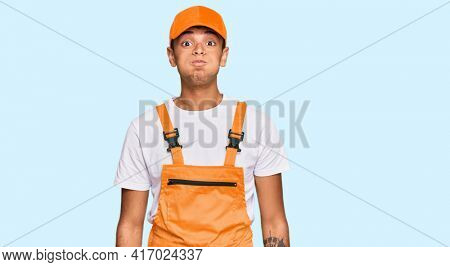 Young handsome african american man wearing handyman uniform puffing cheeks with funny face. mouth inflated with air, crazy expression.