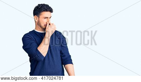 Young hispanic man wearing casual clothes smelling something stinky and disgusting, intolerable smell, holding breath with fingers on nose. bad smell