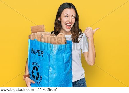 Young beautiful woman holding recycling wastebasket with paper and cardboard pointing thumb up to the side smiling happy with open mouth