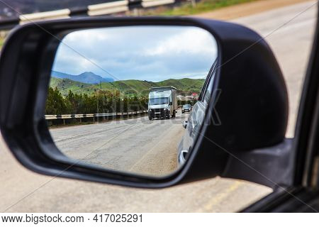 View Through The Rearview Mirror Of The Car On The Movement Of Cars On A Country Highway
