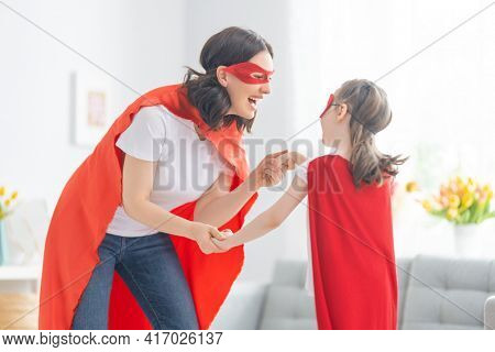 Mother and her child playing together. Girl and mom in Superhero costume. Mum and kid having fun. Family holiday and togetherness.