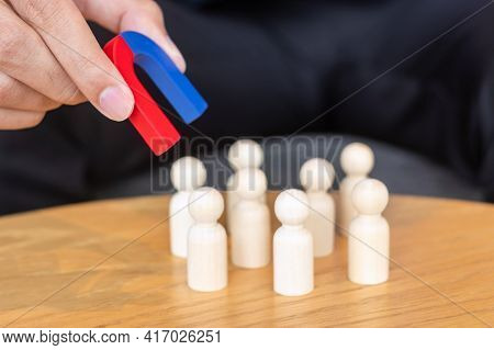 Businessman Hand Holding Magnet And Pulling Man Wooden Figure From The Crowd Employee. Business, Hum