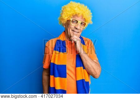 Senior hispanic man football hooligan cheering game smiling looking confident at the camera with crossed arms and hand on chin. thinking positive.