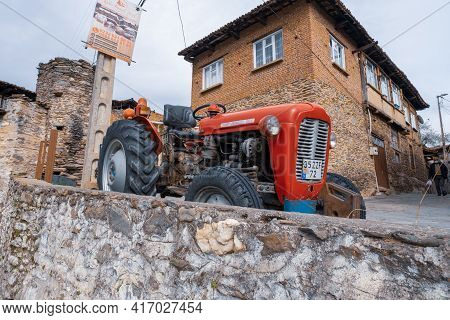 Birgi, Izmir, Turkey - 03.09.2021: Old Red Tractor Parked In A Street And Local Stone Houses In Birg