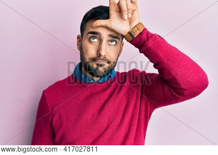 Young hispanic man wearing casual clothes making fun of people with fingers on forehead doing loser gesture mocking and insulting.