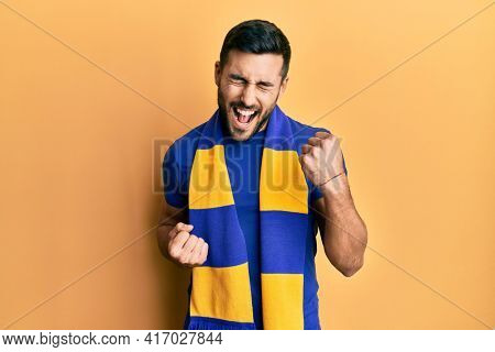 Young hispanic man football hooligan cheering game celebrating surprised and amazed for success with arms raised and eyes closed