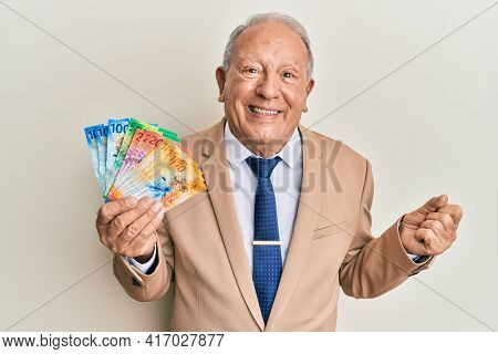 Senior caucasian man holding swiss franc banknotes screaming proud, celebrating victory and success very excited with raised arm