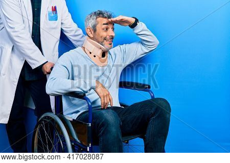 Handsome middle age man with grey hair on wheelchair wearing cervical collar very happy and smiling looking far away with hand over head. searching concept.
