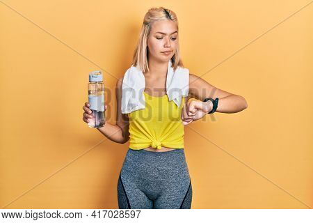 Beautiful blonde sports woman using smart watch skeptic and nervous, frowning upset because of problem. negative person.