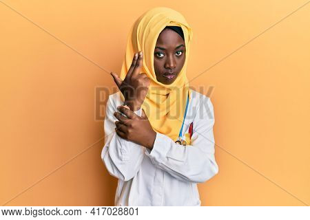 Beautiful african young woman wearing doctor uniform and hijab holding symbolic gun with hand gesture, playing killing shooting weapons, angry face