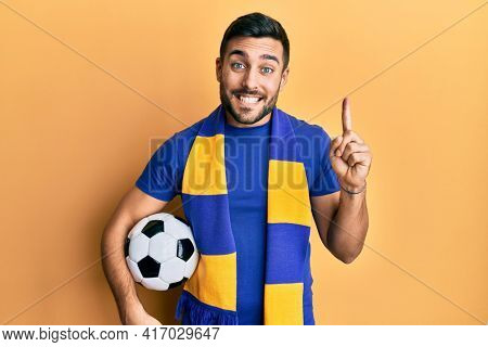 Young hispanic man football hooligan soccer ball smiling with an idea or question pointing finger with happy face, number one