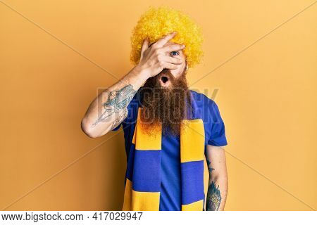 Redhead man with long beard football hooligan cheering game wearing funny wig peeking in shock covering face and eyes with hand, looking through fingers with embarrassed expression.