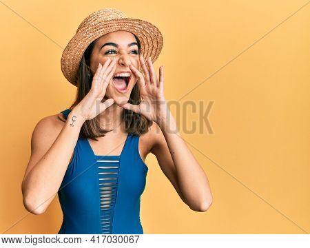 Young brunette girl wearing swimsuit and summer hat shouting angry out loud with hands over mouth