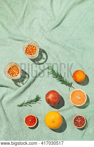 Summer Scene With Fruits,rosemary And Glasses Of Water Or Lemonade On Pastel Green Beach Towel. Drin