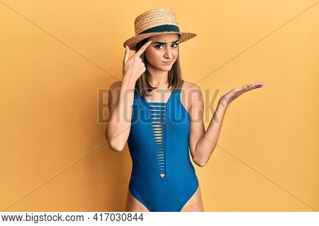 Young brunette girl wearing swimsuit and summer hat confused and annoyed with open palm showing copy space and pointing finger to forehead. think about it.
