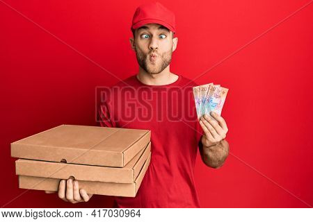 Young caucasian man holding delivery box and swiss franc banknotes making fish face with mouth and squinting eyes, crazy and comical.