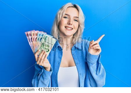 Young blonde girl holding thai baht banknotes smiling happy pointing with hand and finger to the side