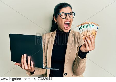 Young hispanic woman wearing business style holding laptop and 50 euros angry and mad screaming frustrated and furious, shouting with anger. rage and aggressive concept.