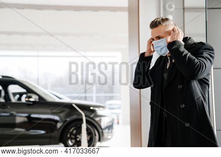 Male customer wearing mask walking in a car dealership