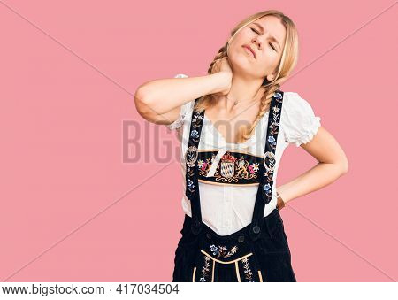 Young beautiful blonde woman wearing oktoberfest dress suffering of neck ache injury, touching neck with hand, muscular pain