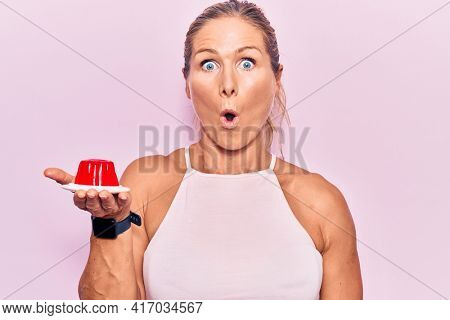 Middle age caucasian blonde woman holding sweet strawberry jelly scared and amazed with open mouth for surprise, disbelief face