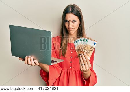 Young beautiful woman holding laptop and 50 euros skeptic and nervous, frowning upset because of problem. negative person.