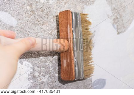 The Repairman Wets Old Wallpaper With Water With A Brush - A Method Of Removing Old Wallpaper From T