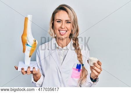 Beautiful young blonde doctor woman holding anatomical model of knee joint and protein powder sticking tongue out happy with funny expression.
