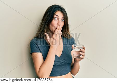 Young caucasian woman drinking glass of water covering mouth with hand, shocked and afraid for mistake. surprised expression