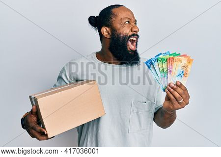 Young african american man holding delivery box and swiss franc banknotes angry and mad screaming frustrated and furious, shouting with anger. rage and aggressive concept.