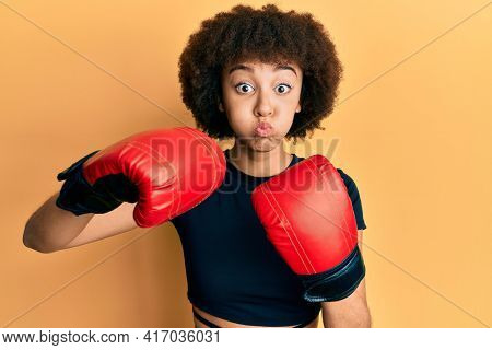 Young hispanic sporty girl using boxing gloves puffing cheeks with funny face. mouth inflated with air, catching air.