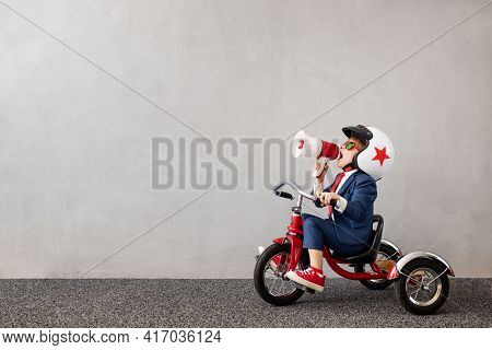 Happy Child Wearing Suit Riding Bicycle Against Grey Concrete Wall Background. Funny Kid Shouting Th